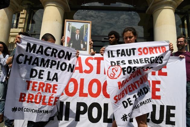 Des manifestants décrochent un portrait du président Macron à la mairie du XIXe arrondissement de Paris le 24 mai 2019