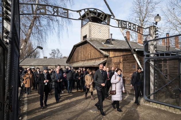 Le Premier ministre français Edouard Philippe entre par le portail d'accès à l'ancien camp de concentration nazi d'Auschwitz (Pologne), le 27 janvier 2020, pour le 75e anniversaire de sa libération