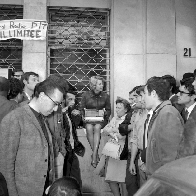 Des grévistes des PTT sont regroupés autour d'un transistor à Paris, le 30 mai 1968, pour écouter l'allocution de Charles de Gaulle