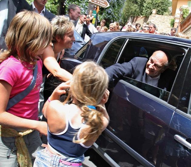 Le président Jacques Chirac salue des personnes le 8 août 2005 après avoir assisté à l'office religieux dominical en l'église de Bormes-les-Mimosas en compagnie de son épouse Bernadette.