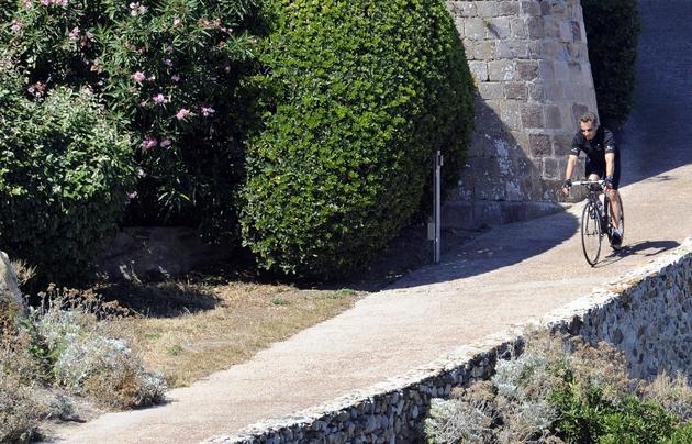 L'ancien président français Nicolas Sarkozy sort à vélo du fort de Brégançon où il passe ses vacances le 23 juillet 2011