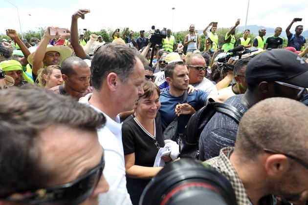 """La ministre des Outre-mer Annick Girardin (C) et le préfet de La Réunion Amaury de Saint-Quentin (C, gauche) arrivent à Sainte-Marie, le 28 novembre 2018, alors que des """"gilets jaunes"""" protestent contre la hausse des prix des carburants et le coût de la"""