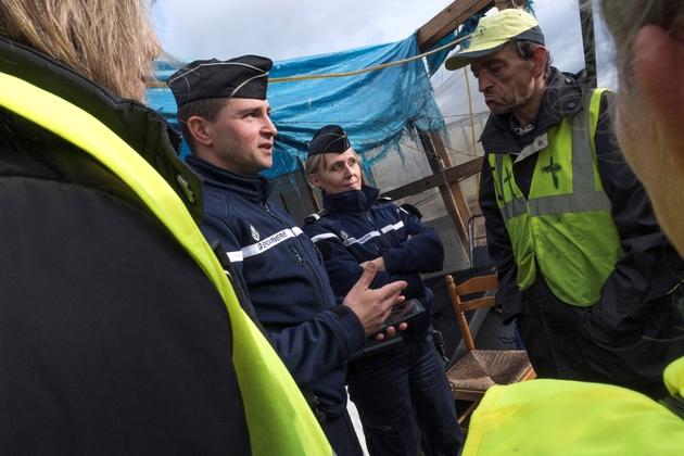 """Des gendarmes s'entretiennent avec des """"gilets jaunes"""" à Saint Beauzire (centre), le 6 décembre 2018"""