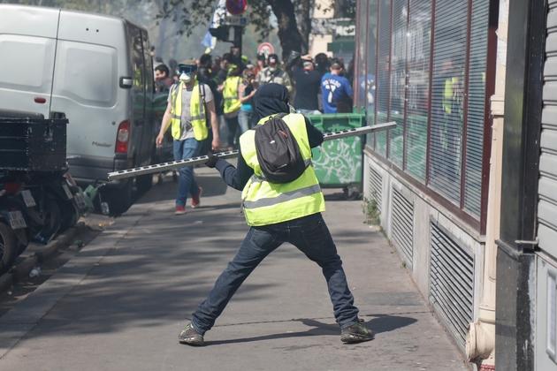 """Un manifestant essaye de casser une vitrine durant la manifestation des """"gilets jaunes"""", le 20 avril 2019 à Paris"""
