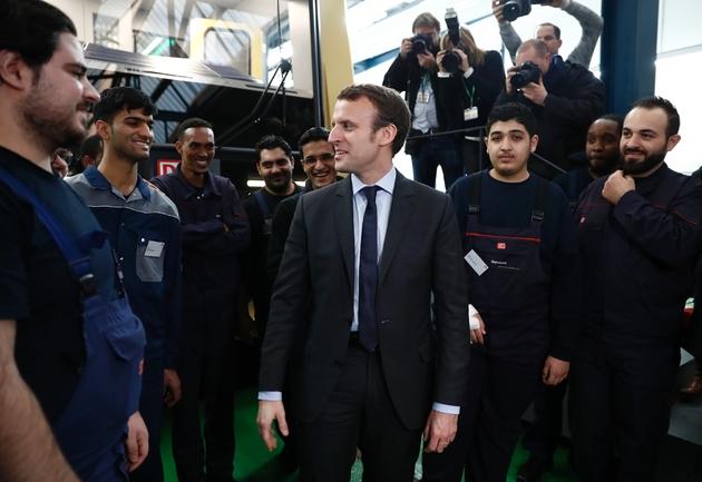 Emmanuel Macron rencontre de jeunes réfugiés sur un site d'apprentissage de la Deutsche Bahn, le 10 janvier 2017, à Berlin.