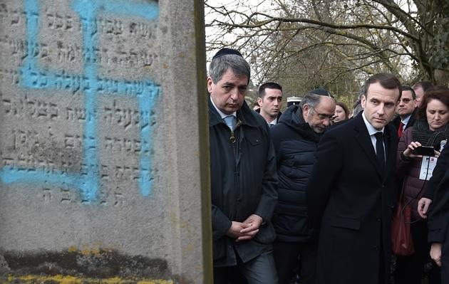 Le président Emmanuel Macron regarde les tombes profanées au cimetière de Quatzenheim, le 19 février 2019 dans le Bas-Rhin