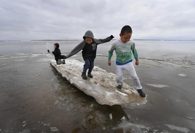 Des enfants jouent sur un morceau de glace près du village eskimau de Yupik, en Alaska (Etats-Unis), le 19 avril 2019