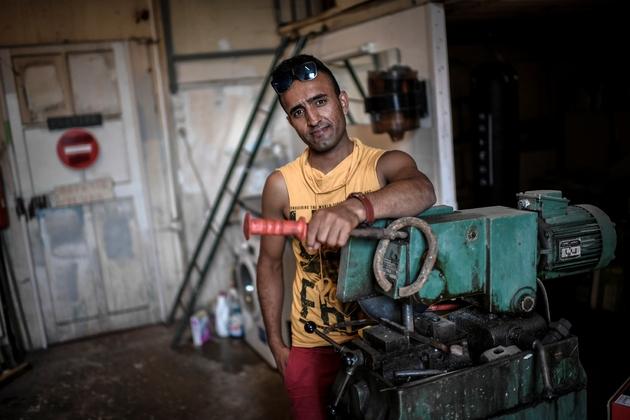 Asif Qaderi, migrant afghan de 23 ans, dans l'atelier de mécanique que lui et d'autres exilés ont contribué à créer dans le centre de Forges-les-Bains (région parisienne)