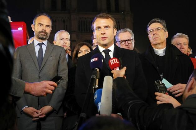 Le Premier ministre Edouard Philippe (G) et le président Emmanuel Macron (C) au pied de Notre Dame après l'incendie qui a ravagé la cathédrale, le 15 avril 2019 à Paris