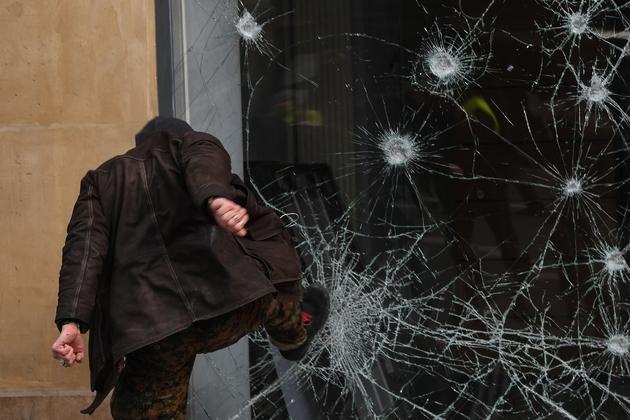 """Un manifestant casse une vitrine de banque à Paris lors de la manifestation des """"gilets jaunes"""" et de la CGT le 5 février 2019"""