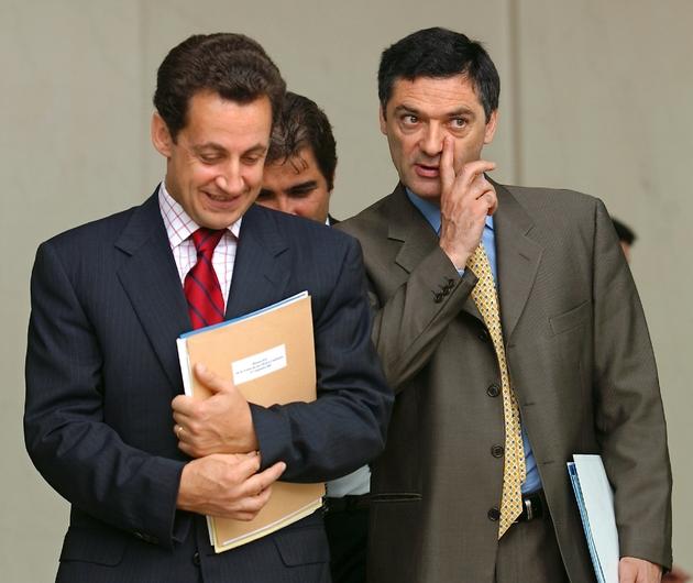 Le ministre de l'Intérieur Nicolas Sarkozy (g) et le ministre délégué aux Liberté locales Patrick Devedjian à la sortie de l'Elysée en septembre 2002 à Paris