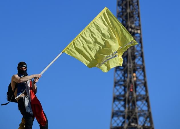 """Un manifestant agite un drapeau jaune lors du vingtième samedi consécutif d'action des """"gilets jaunes"""" à Paris, le 30 mars 2019"""