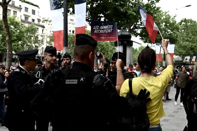Des gendarmes entourent une jeune femme habillée en jaune criants des slogans anti-Macron, lors du défilé du 14 juillet 2019 sur les Champs-Elysées à Paris