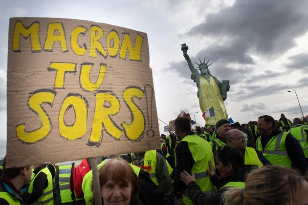 """Des """"gilets jaunes"""" à Colmar, le 2 mars 2019, réclament le départ d'Emmanuel Macron, près d'une réplique de la Statue de la Liberté vêtue d'un gilet jaune"""