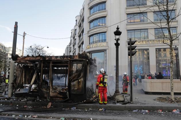 """Des pompiers près d'un kiosque à journaux incendié lors de la manifestation des """"gilets jaunes"""" sur les Champs-Elysées, le 16 mars 2019 à Paris"""