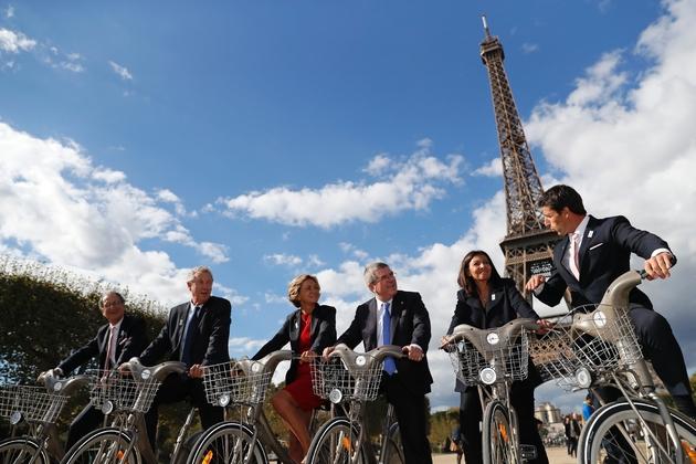 Valérie Pécresse et la maire de Paris Anne Hidalgo entourées des champions Guy Drut et Tony Estanguet sur des Vélib à Paris le 2 octobre 2016