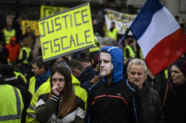 """Des """"gilets jaunes"""" à Lyon, le 2 mars 2019, réclament une """"justice fiscale"""". Un homme porte un masque à l'effigie d'Emmanuel Macron"""
