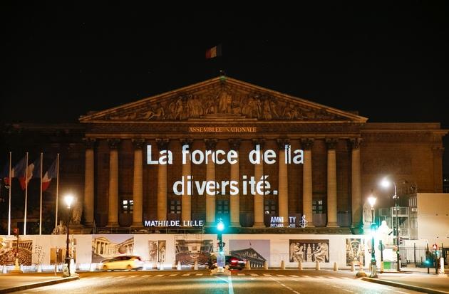 """Une des """"raisons"""" d'accueillir les migrants projetées sur la façade de l'Assemblée nationale par Amnesty International France, à Paris le 19 juin 2018"""