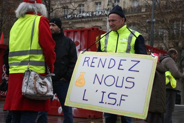 """Un """"gilet jaune"""" milite avec une pancarte pour le rétablissement de l'ISF, le 1er décembre 2018 Place de la République à Paris"""