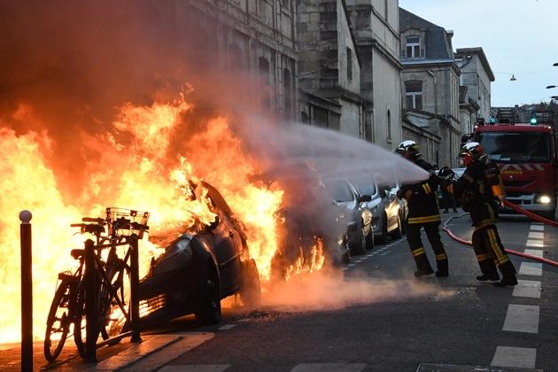 """Des pompiers interviennent sur des véhicules incendiés en marge d'une manifestation de """"gilets jaunes"""", le 9 février 2019 à Bordeaux"""