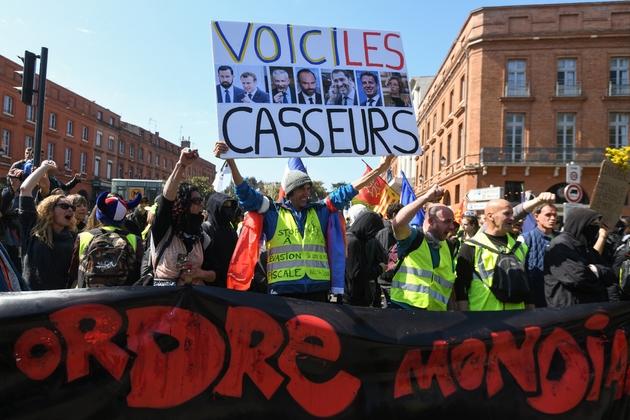 """Jean-Baptiste Reddé, figure familière des manifestations parisiennes connu sous le pseudonyme """"Voltuan"""", brandit une pancarte lors de la manifestation des """"gilets jaunes"""" à Toulouse le 13 avril 2019"""
