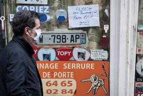 Commerces fermés : le 6 avril 2020 à Paris, un homme passe devant une vitrine de commerce fermé.